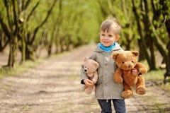 一个可爱,微笑的男孩坐与玩具熊的椅子春天 榛树 免版税库存图片
