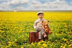 一个可爱,微笑的男孩坐有玩具熊的箱子春天 榛树 库存照片