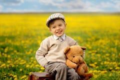 一个可爱,微笑的男孩坐有玩具熊的箱子春天 榛树 库存图片