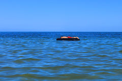 一个可膨胀的床垫的人在海 免版税库存图片