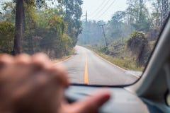 一个司机的手在一辆汽车的方向盘的在路的 免版税库存图片
