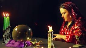 一个吉普赛人在烛光的算命交谊厅计划占卜的卡片在桌上 影视素材