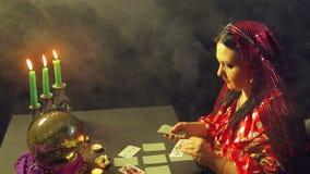 一个吉普赛人在烛光的算命交谊厅计划占卜的卡片在桌上 股票视频