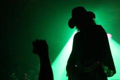 一个吉他弹奏者的剪影阶段的与有爱好者的拳头的一个牛仔帽在绿色反射器前面 库存照片