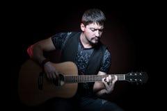 一个吉他弹奏者的画象有声学吉他的 免版税库存图片