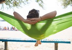一个吊床的年轻愉快的妇女在海滩 库存图片