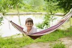 一个吊床的男孩在自然 库存照片