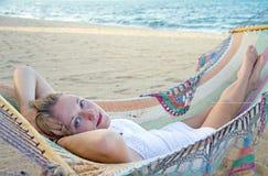 一个吊床的美丽的妇女在海滩 免版税库存图片