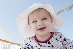 一个吊床的美丽的愉快的传神白肤金发的女孩小孩在海滩 免版税库存照片