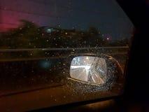 一个后视镜的迷离图片从汽车里边的有在玻璃窗的雨的,当驾驶汽车时 库存图片