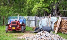 一个后院的农村场面有拖拉机和木头堆的 免版税图库摄影