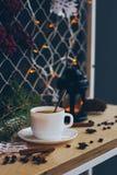 一个咖啡杯有在木表面上的圣诞灯背景与锥体、绿色分支、咖啡豆和火炬 免版税图库摄影