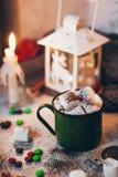 一个咖啡杯用在圣诞灯背景的可可粉用蛋白软糖 库存图片