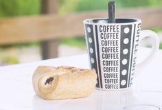 一个咖啡杯用在桌,乡间别墅,一张被定调子的照片的游廊上的一个新月形面包 免版税库存图片