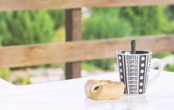 一个咖啡杯用在桌,乡间别墅,一张被定调子的照片的游廊上的一个新月形面包 库存照片