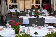 一个咖啡馆大阳台的街道视图与桌和椅子的在红葡萄酒 图库摄影