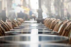 一个咖啡馆大阳台的街道视图与空的桌和椅子的 免版税库存照片