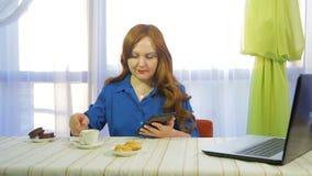 一个咖啡馆的一名棕色毛发的妇女在桌上与片剂和饮料咖啡一起使用 股票视频