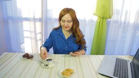 一个咖啡馆的一名棕色毛发的妇女在桌上与片剂和饮料咖啡一起使用 股票录像
