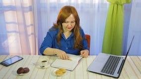 一个咖啡馆的一名棕色毛发的妇女在桌上与膝上型计算机和饮料咖啡一起使用 股票录像