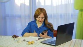 一个咖啡馆的一名棕色毛发的妇女在桌上与膝上型计算机和饮料咖啡一起使用 股票视频
