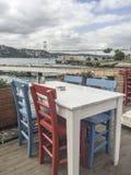 一个咖啡馆的五颜六色的木椅子和桌由海的 库存图片