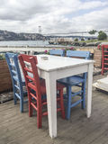 一个咖啡馆的五颜六色的木椅子和桌由海的 免版税库存图片