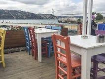 一个咖啡馆的五颜六色的木椅子和桌由海的 库存照片