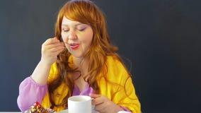 一个咖啡馆的女孩在桌饮用的茶和吃蛋糕 影视素材