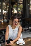 一个咖啡馆的女性用早晨咖啡 免版税库存图片