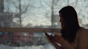 一个咖啡馆的由窗口的少妇与电话和饮料 午休 股票视频