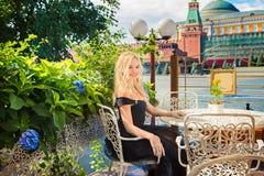 一个咖啡馆的白肤金发的女孩在红场微笑 expec的概念 免版税库存图片