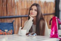 一个咖啡馆的迷人的妇女一杯咖啡的 免版税库存照片