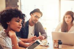 一个咖啡馆的青年人与膝上型计算机和数字式片剂 免版税库存照片