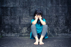 一个哀伤的亚裔女孩的画象对难看的东西墙壁 免版税库存照片