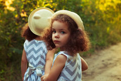 一个哀伤的卷曲小女孩和她的双姐妹的画象 在头的一个帽子 画象的室外关闭 女孩转过来 免版税图库摄影