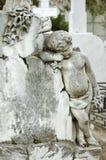 一个哀伤的天使孩子的公墓雕象 免版税库存照片