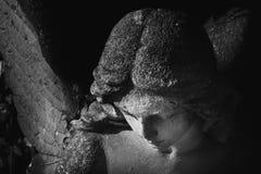 一个哀伤的天使的葡萄酒图象在一座公墓的反对backgroun 库存图片