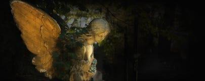 一个哀伤的天使的葡萄酒图象在一座公墓的反对backgroun 免版税库存照片