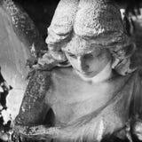 一个哀伤的天使的葡萄酒雕象在一座公墓的反对backgrou 免版税库存图片