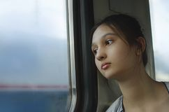 一个哀伤的女孩坐火车 免版税库存照片