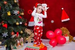 一个哀伤的孩子支持圣诞树 库存图片