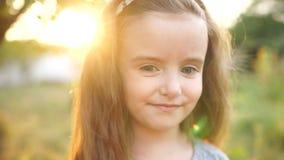 一个哀伤的小女孩的一张接近的画象有长的头发和大灰色眼睛的 婴孩是窘迫,害羞和哀伤的 风 股票录像