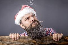 一个哀伤的有胡子的人的特写镜头画象有查寻圣诞老人的盖帽的 免版税图库摄影