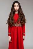 一个哀伤的深色的女孩的画象有长的头发的在一件红色礼服 免版税库存图片