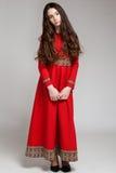 一个哀伤的深色的女孩的画象有长的头发的在一件红色礼服 免版税库存照片