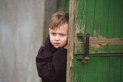 一个哀伤的男孩看从门的后面 库存照片