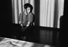 一个哀伤的皱眉的男孩坐地板 库存图片