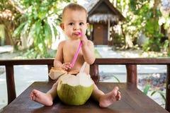一个哀伤的矮小的一岁的孩子坐从新鲜的绿色椰子的木桌和饮料椰奶通过秸杆 免版税库存图片