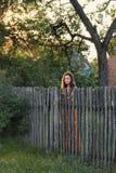 一个哀伤的预期女孩在村庄服装的木木栅后站立 免版税库存照片